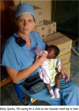 Betty Spaks, RN caaring for a child on her disaster relief trip to Haiti.